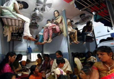 people sitting on luggage racks in Indian railway coaches